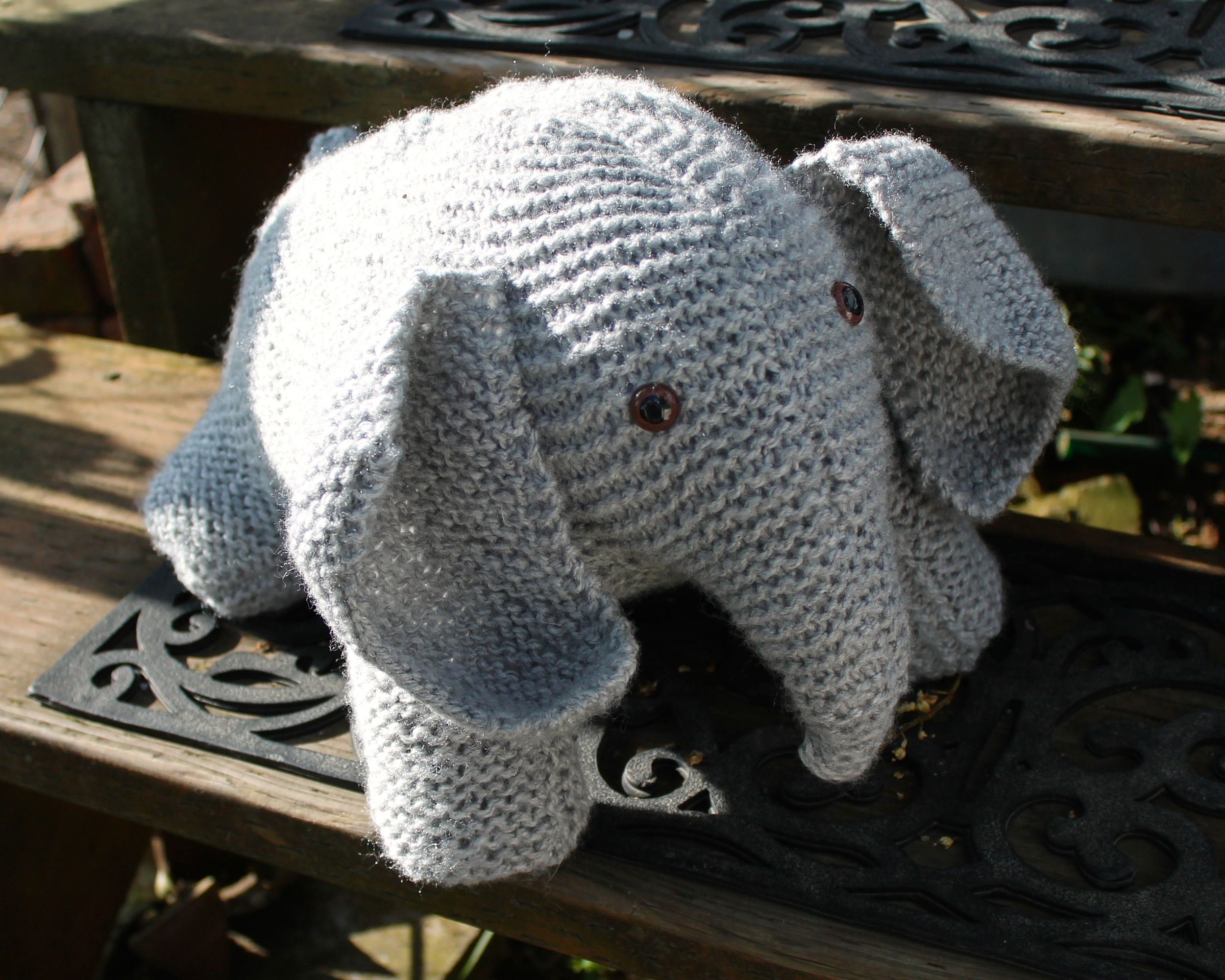 Gray knit stuffed elephant with brown glass eyes, sitting on porch steps
