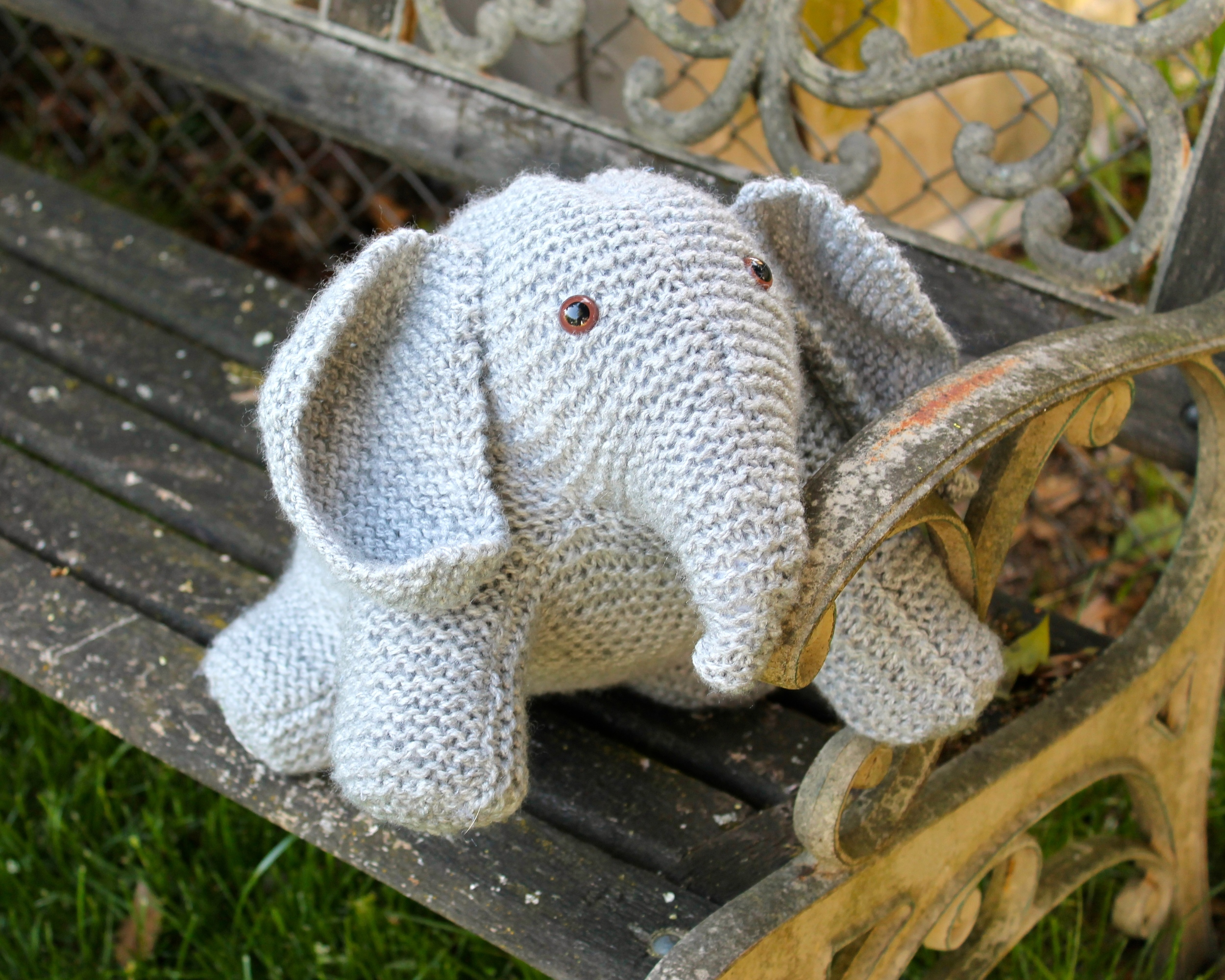 Gray knit stuffed elephant with brown glass eyes, sitting in a bench