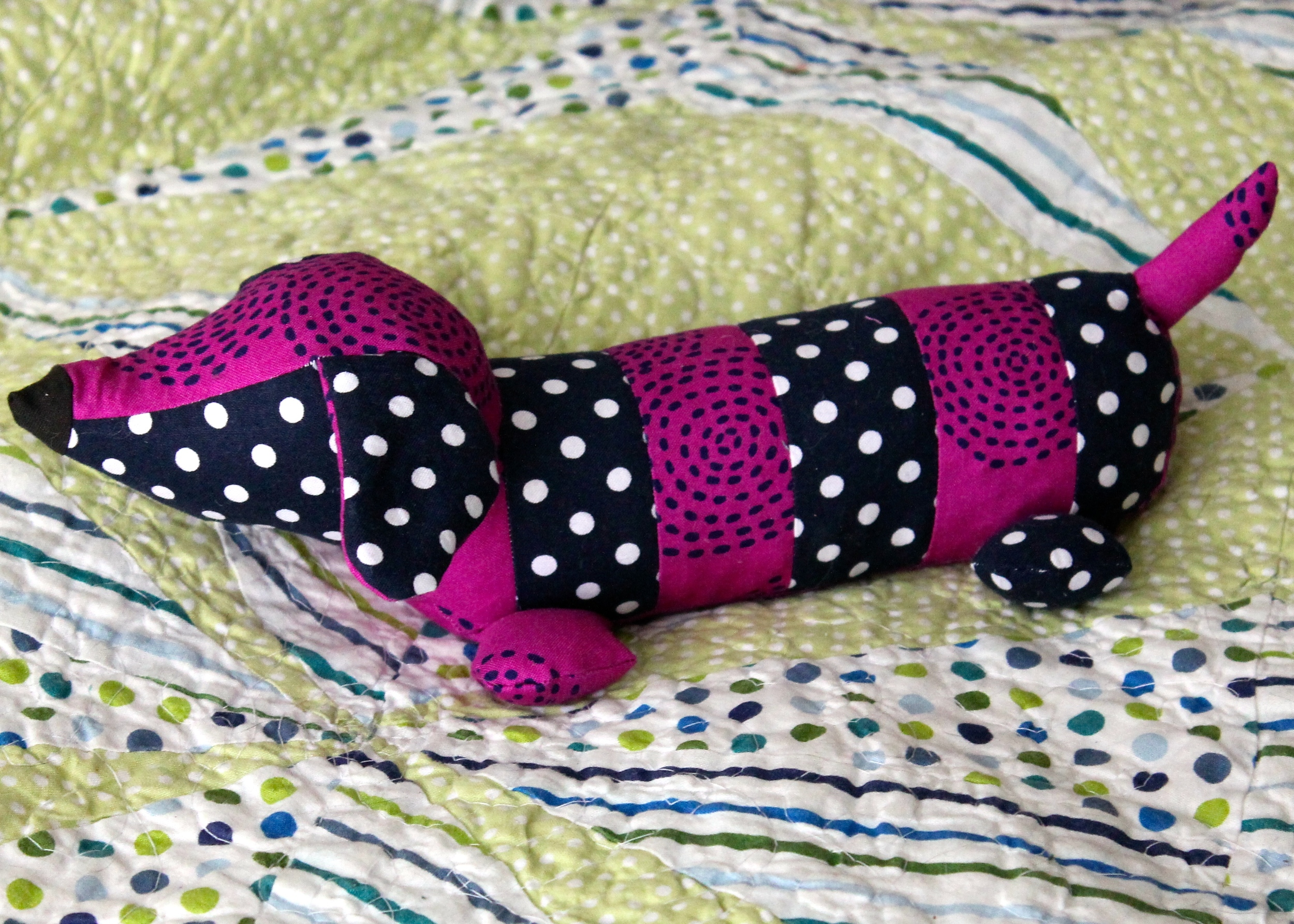Stuffed dachshund with alternating purple and blue and white fabric