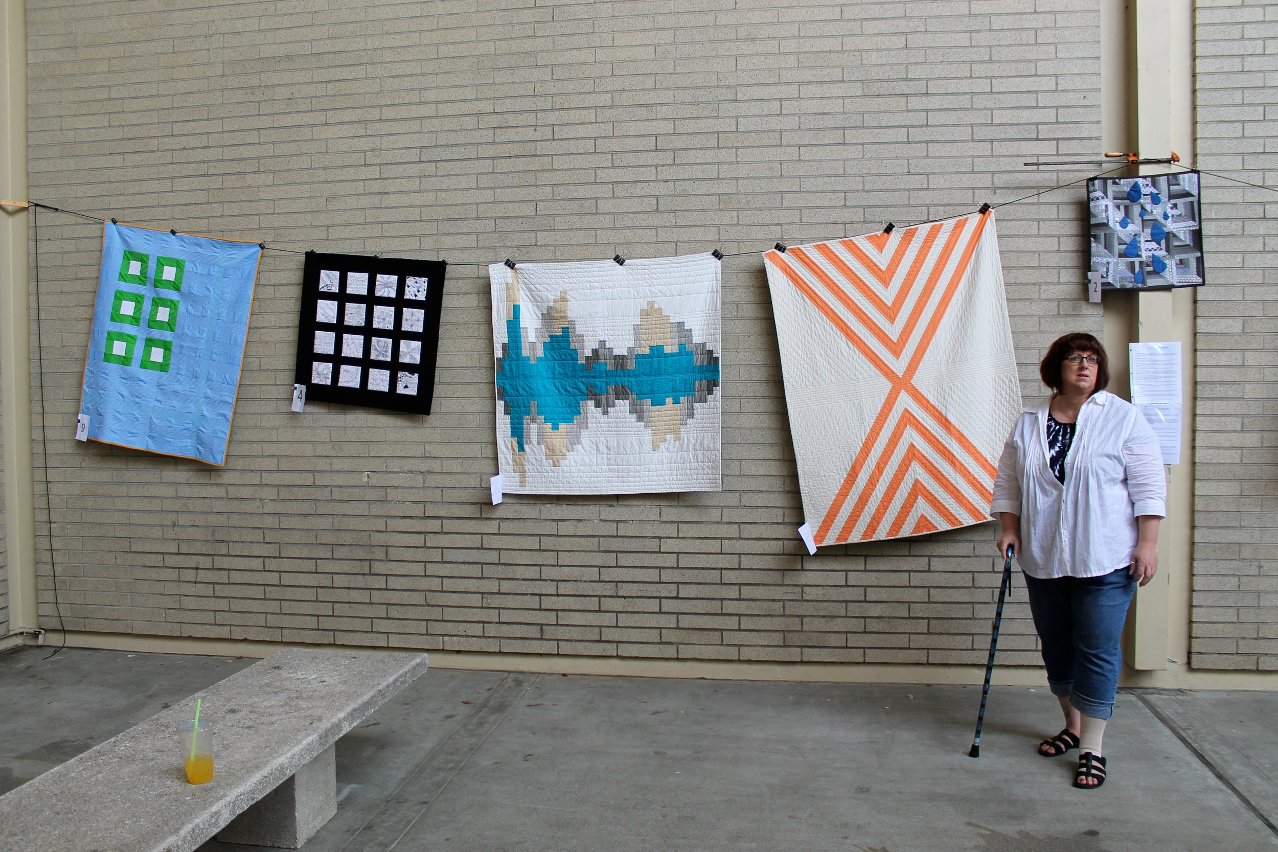 Woman standing in front of assortment of modern quilts at Northwest Folklife (from Seattle Modern Quilt Guild)