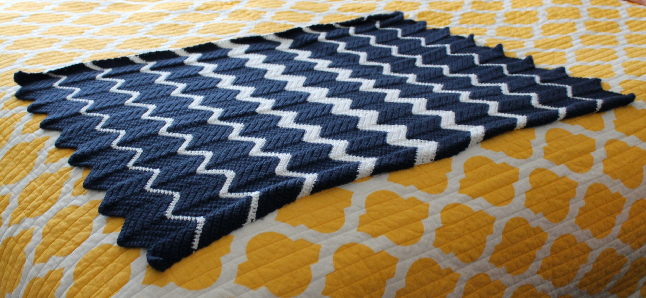 Crocheted blanket with navy and white zig zag stripes