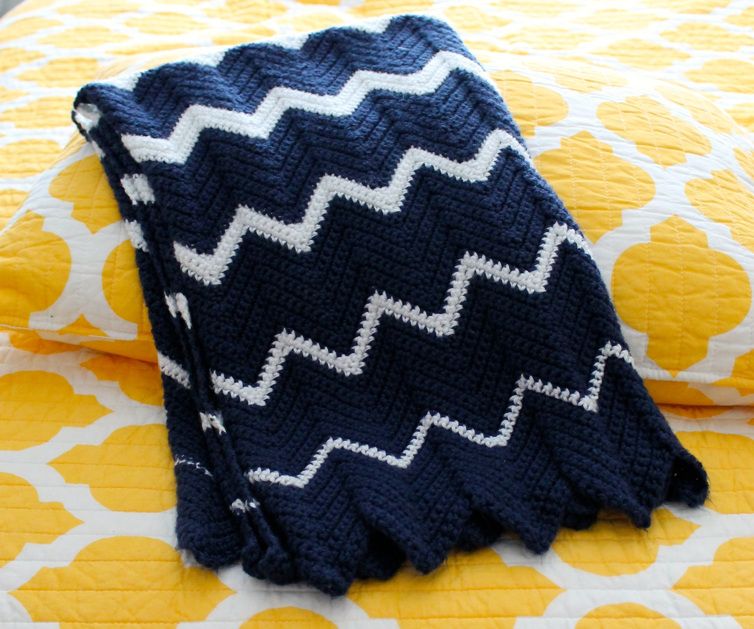 crocheted blanket with navy and white zig zag stripes, folded, laying on a yellow background