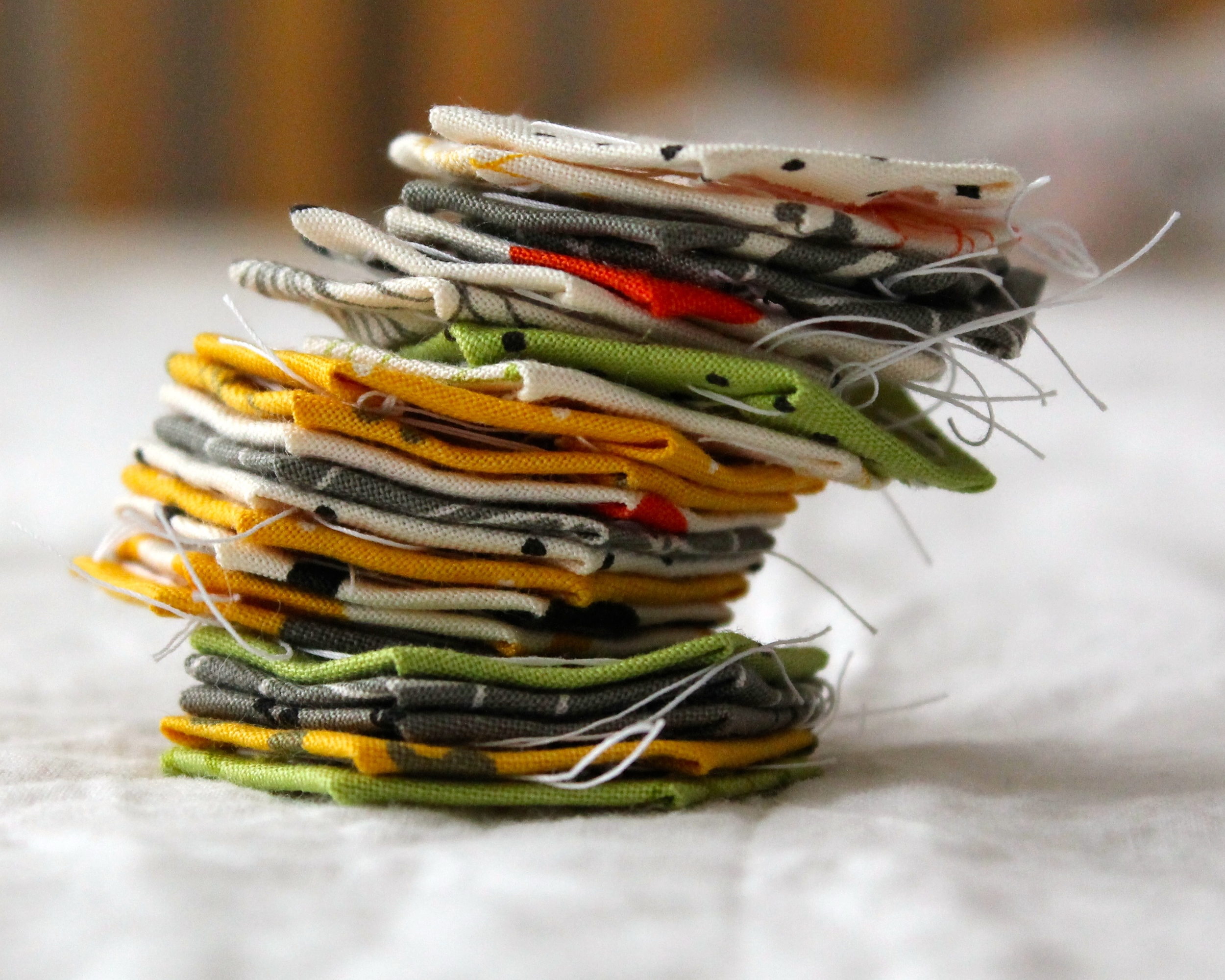 paper pieced hexagons in yellow, green, gray, white, and orange fabric, in a stack