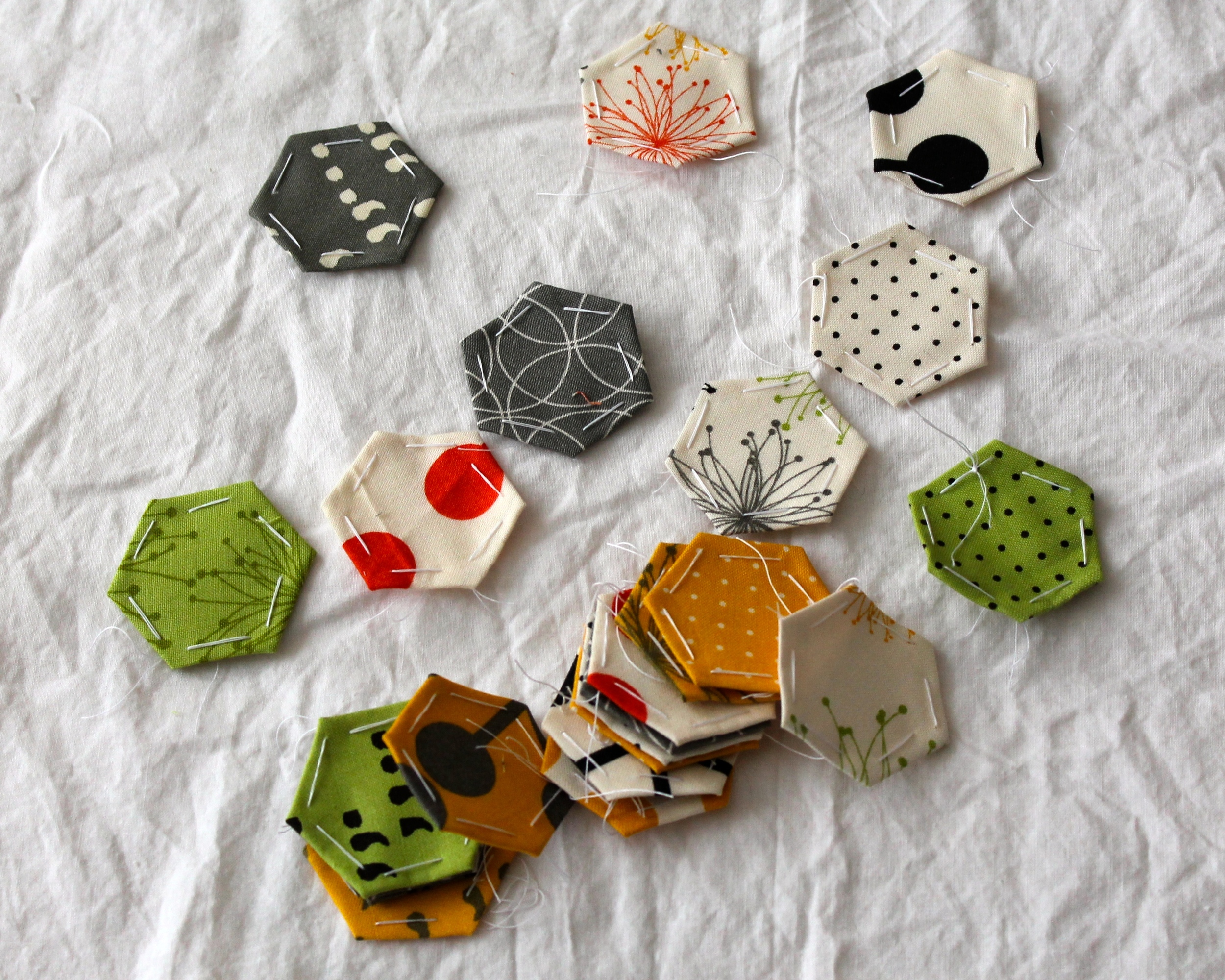 Scattered paper pieced hexagons in yellow, green, gray, white, and orange fabric