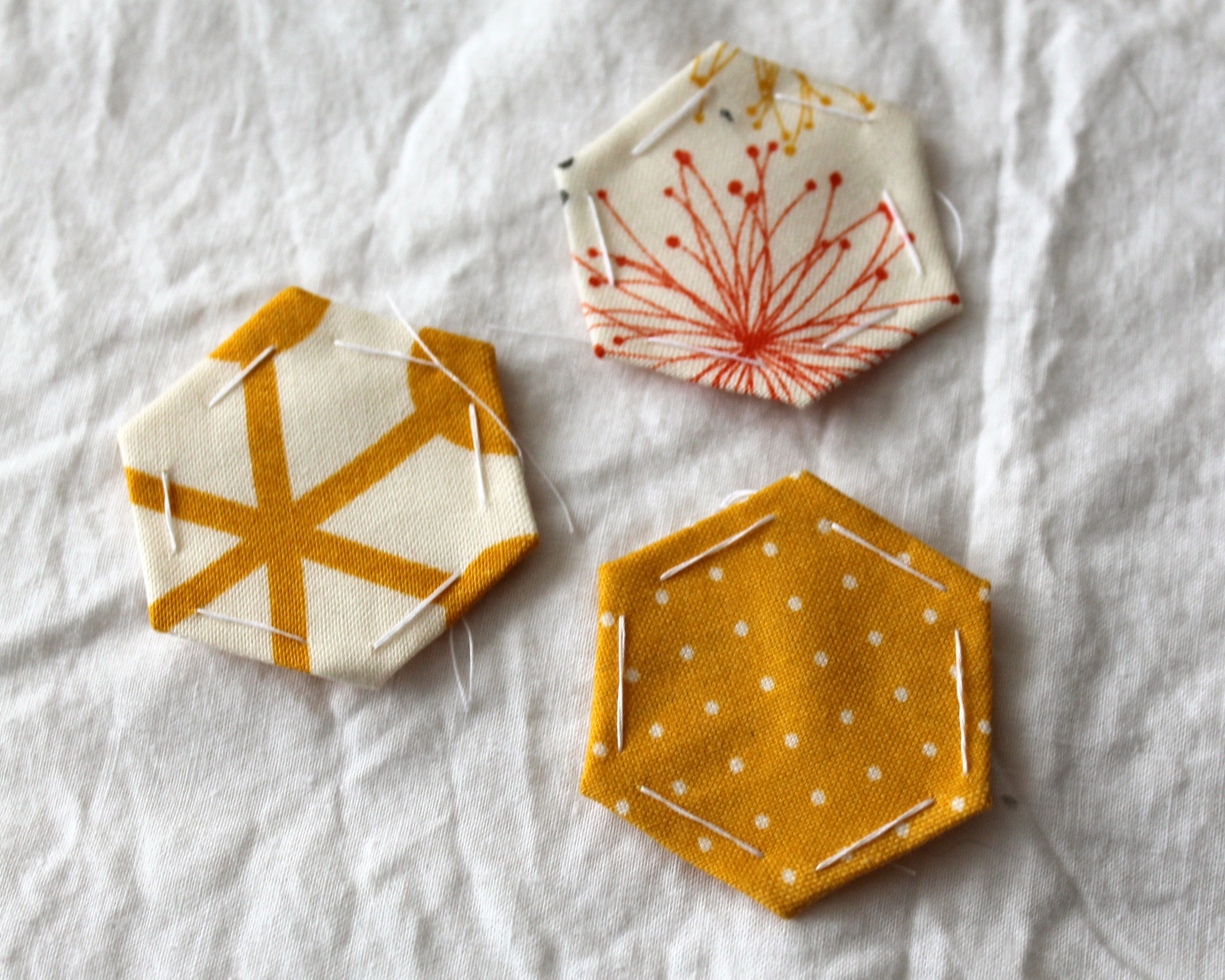 three paper pieced hexagons in white, orange, and yellow fabric
