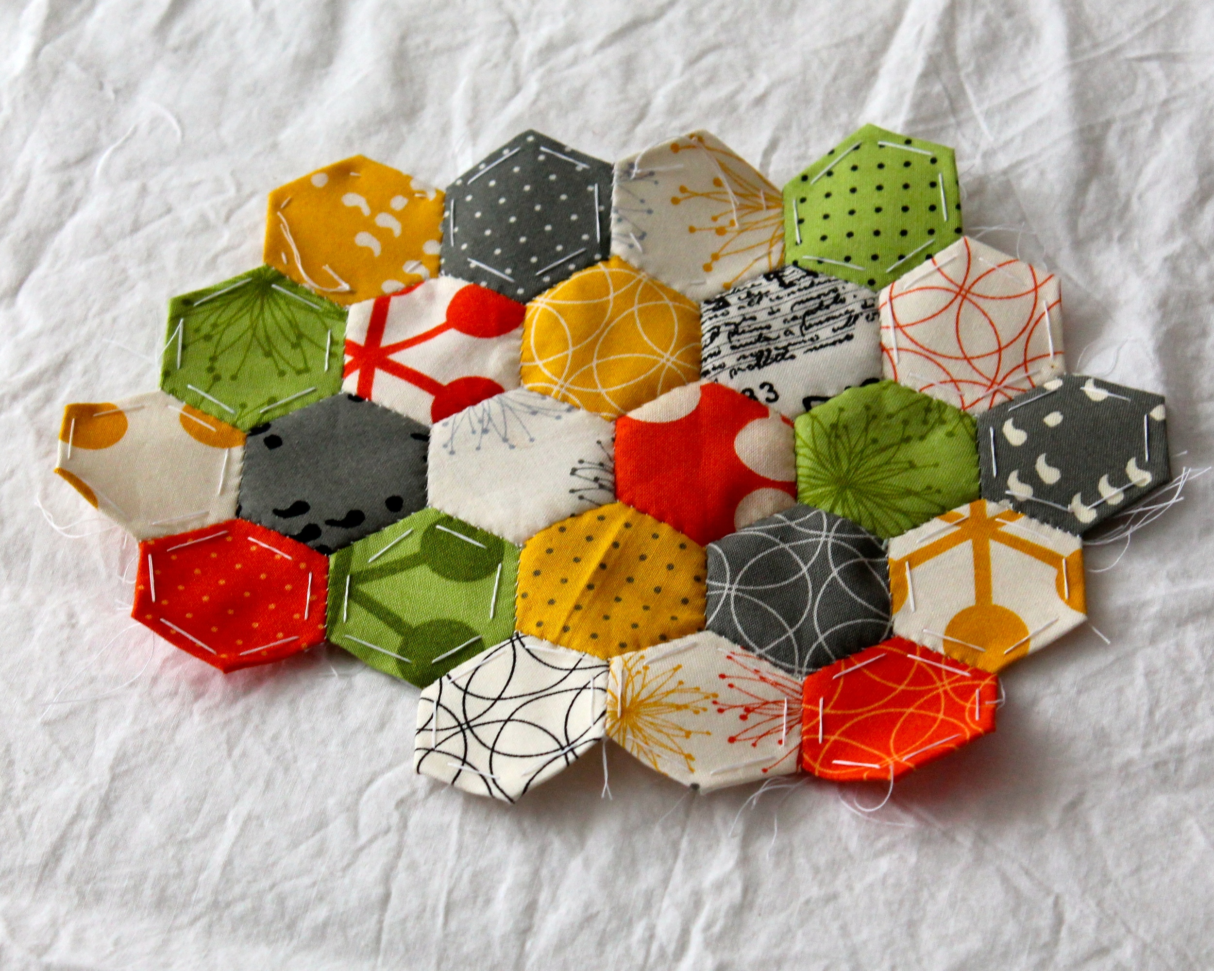 paper pieced hexagons in yellow, green, gray, white, and orange fabric
