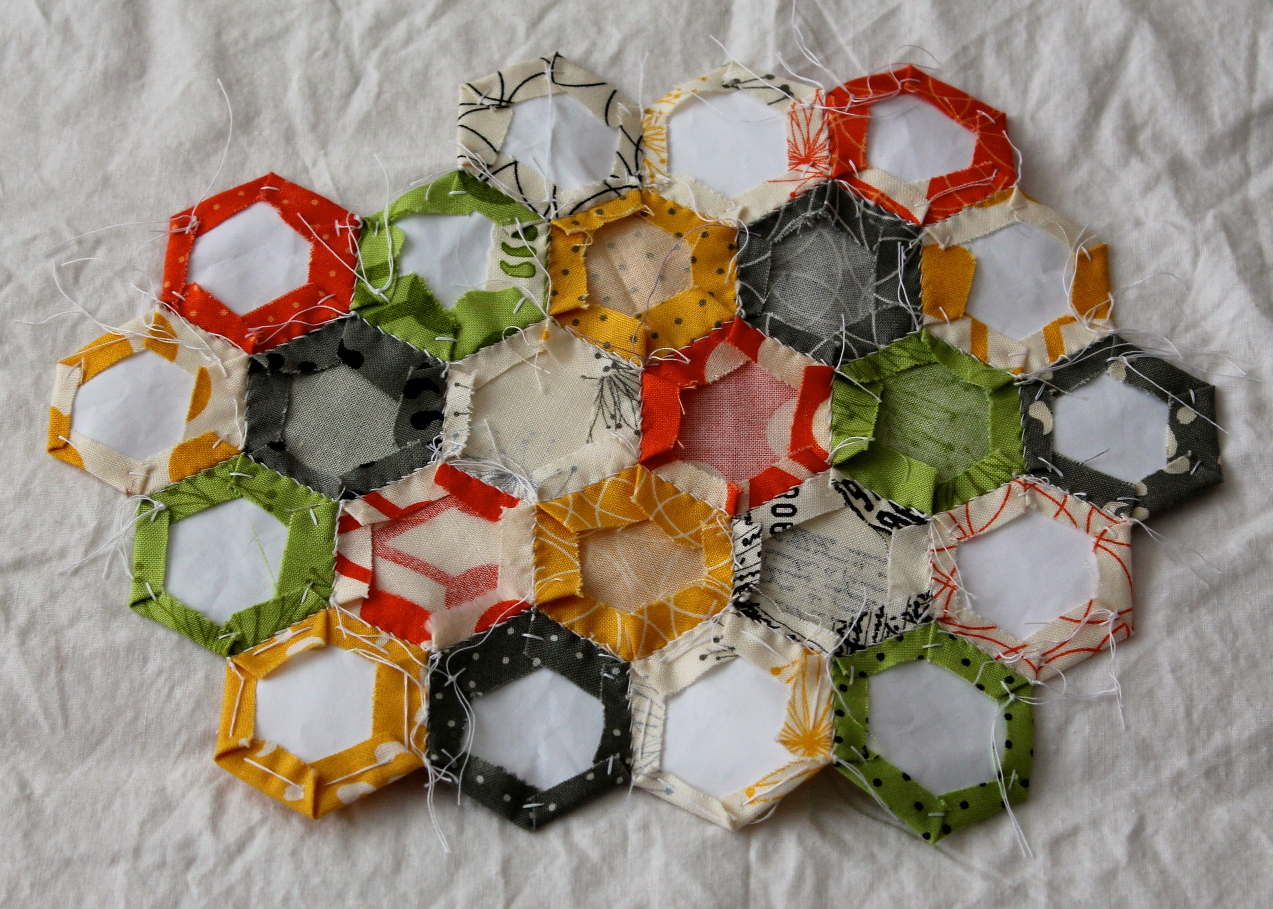 the back of paper pieced hexagons in yellow, green, gray, white, and orange fabric