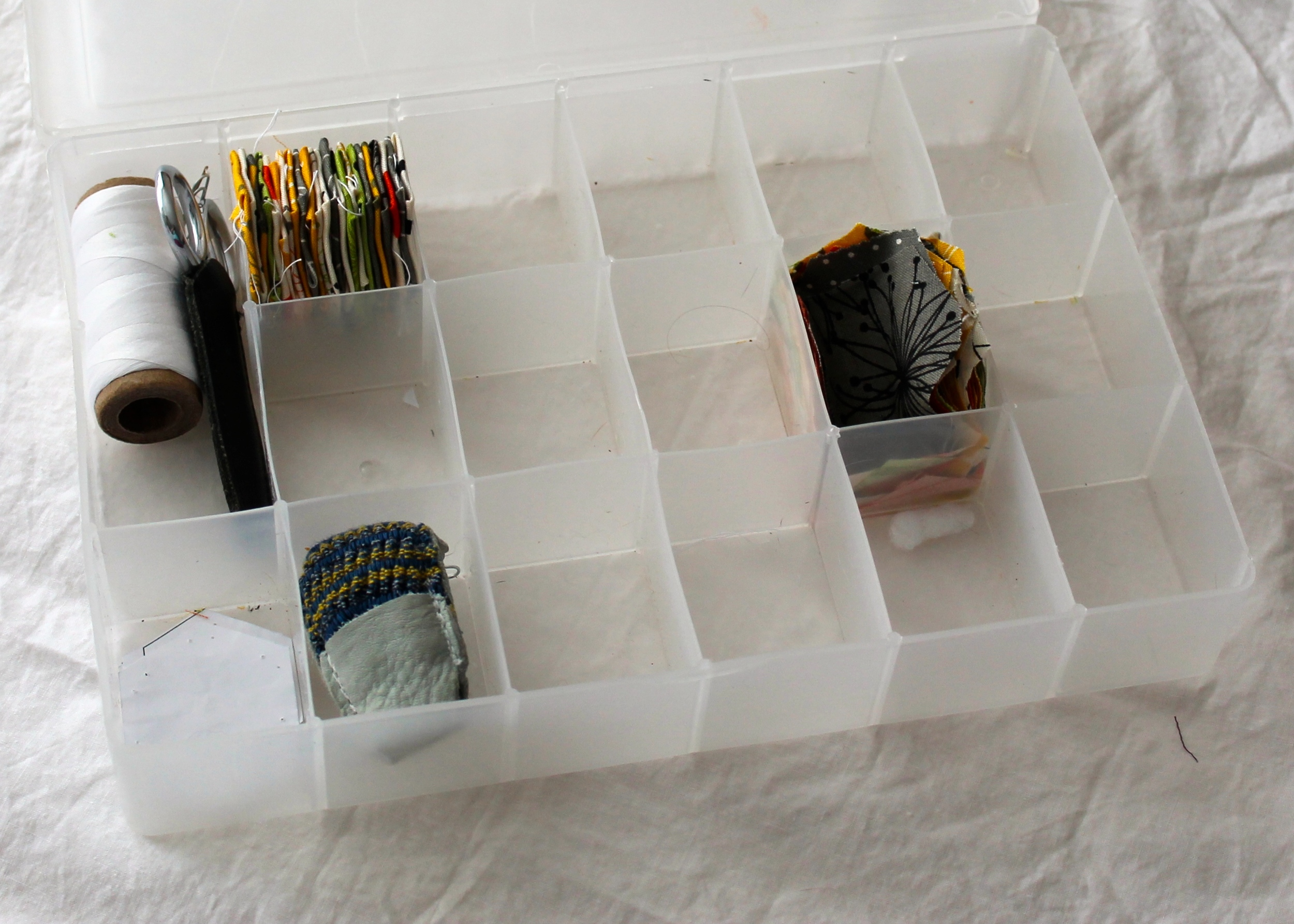 paper pieced hexagons, thread, and a thimble in a carrying case