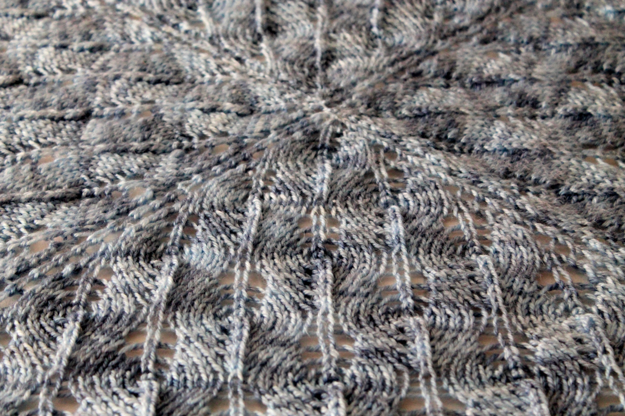 Close up of blue hand knit lacy baby blanket, made with Cascade Yarns