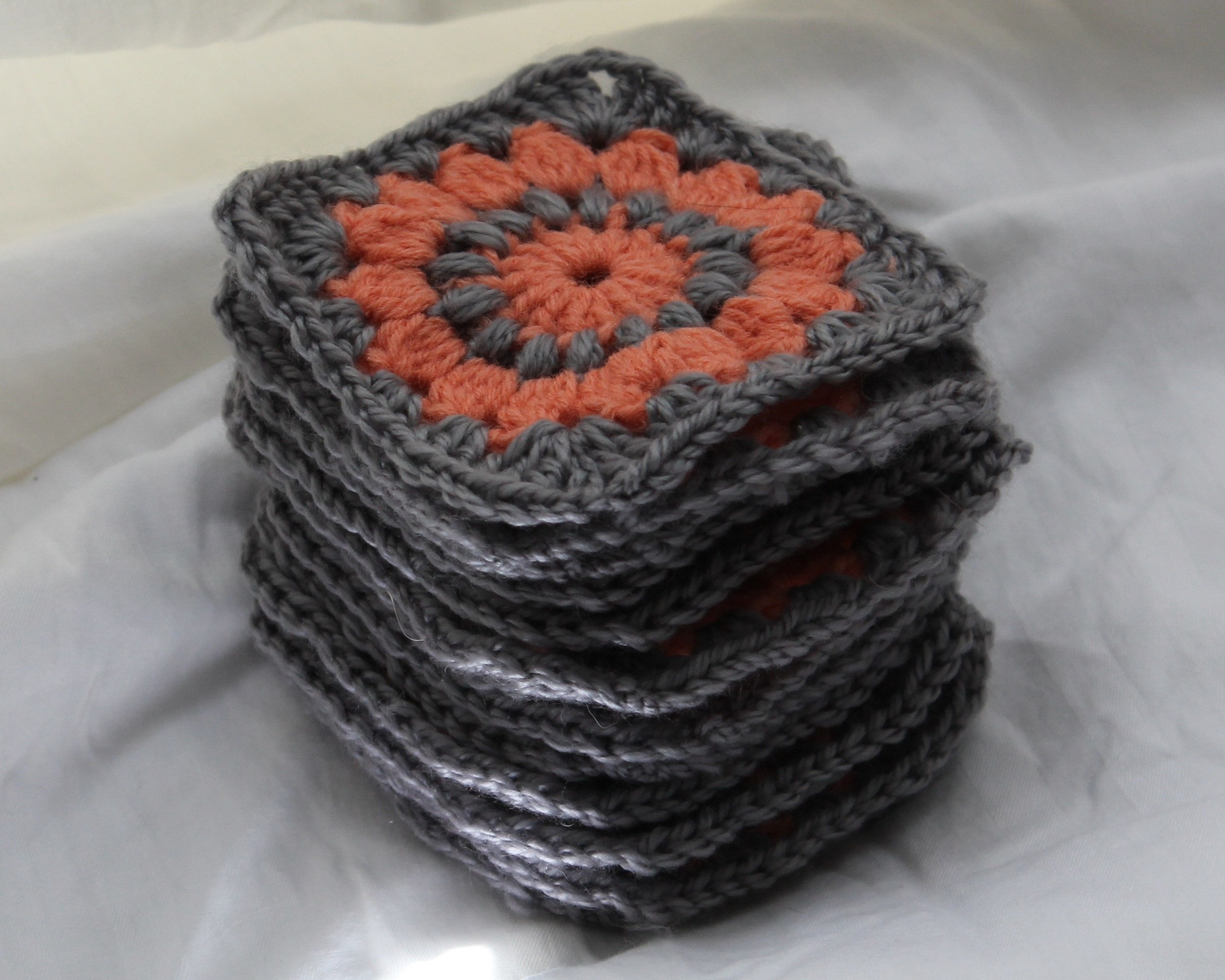 Coral and gray granny squares in a stack