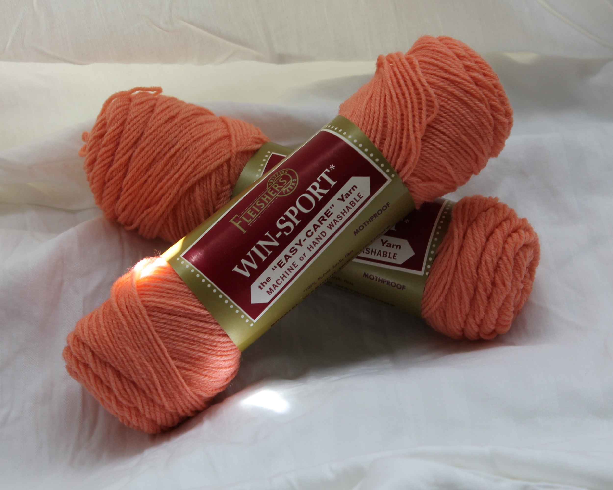 Two coral colored skeins of yarn