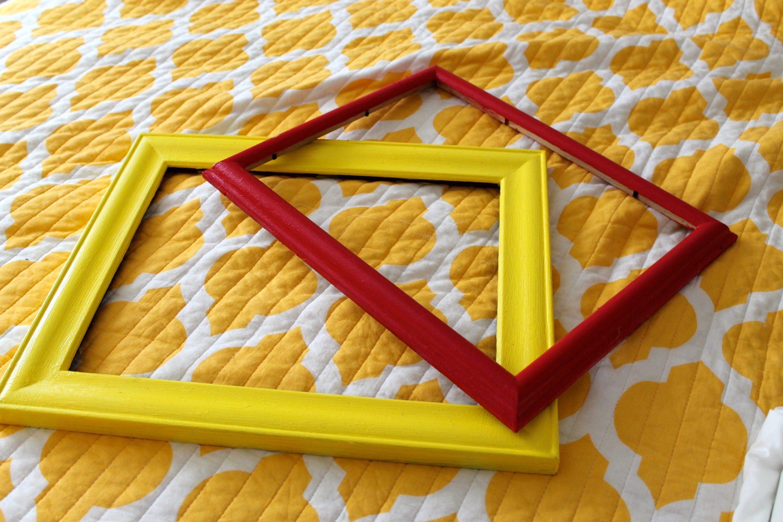 Thrift store picture frames after being painted, one red, one yellow