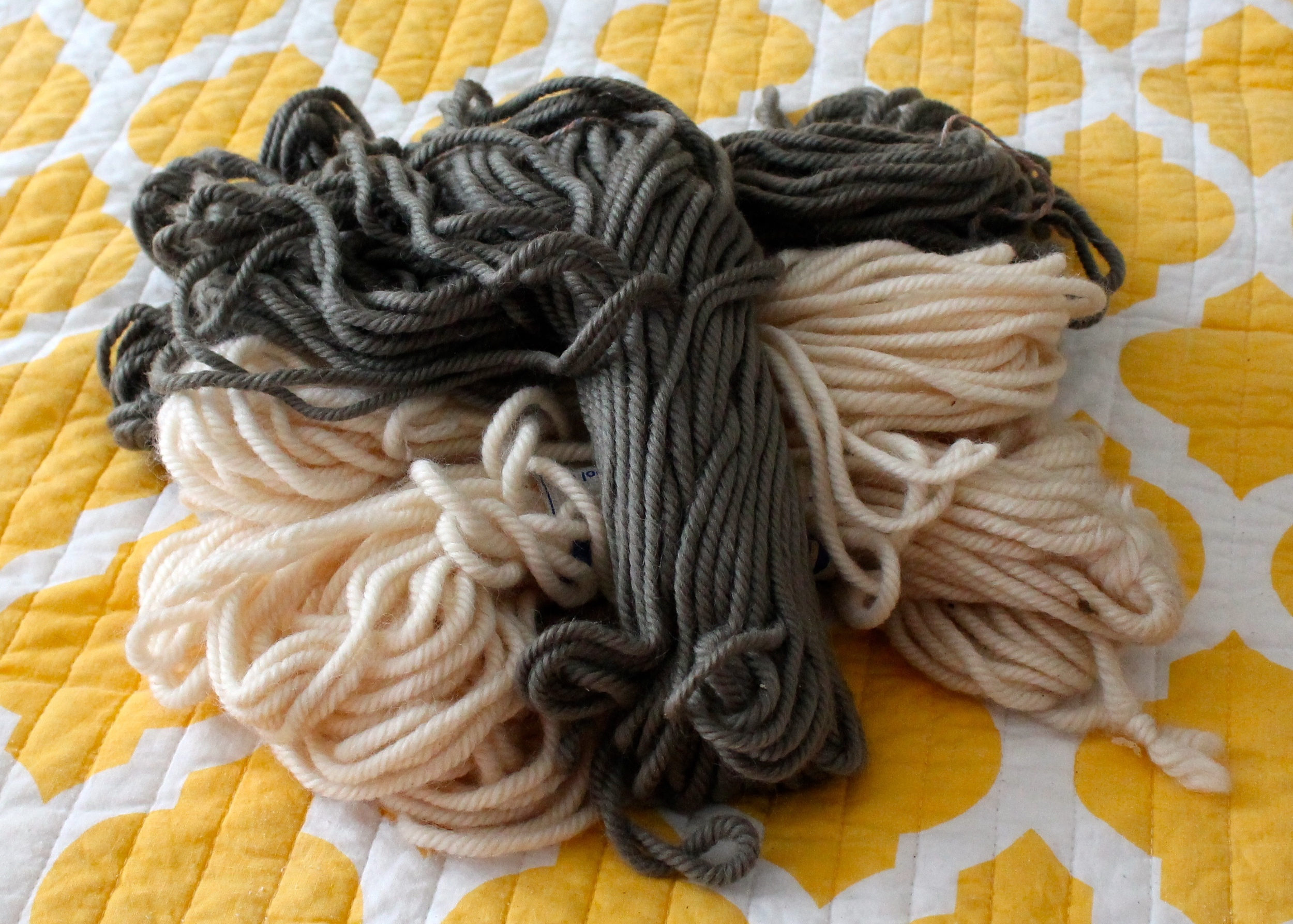 Pile of wool yarn in gray and cream