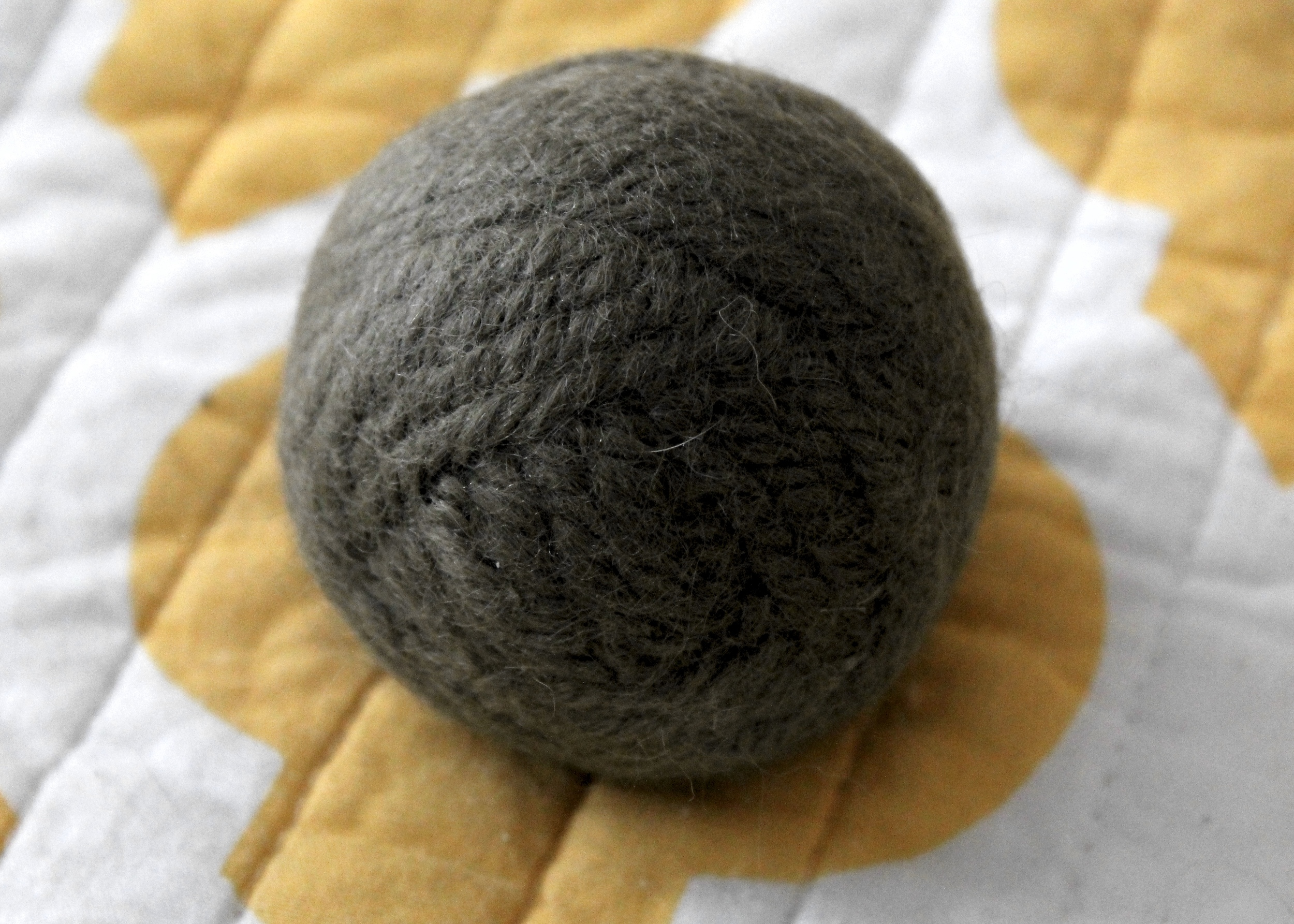 Gray homemade dryer ball made from wool yarn on a yellow and white background