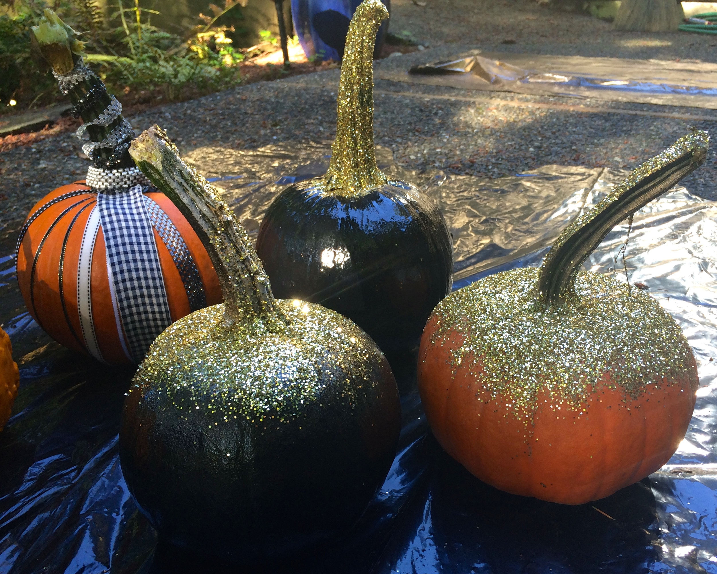 Pumpkins decorated with paint and glitter and ribbons