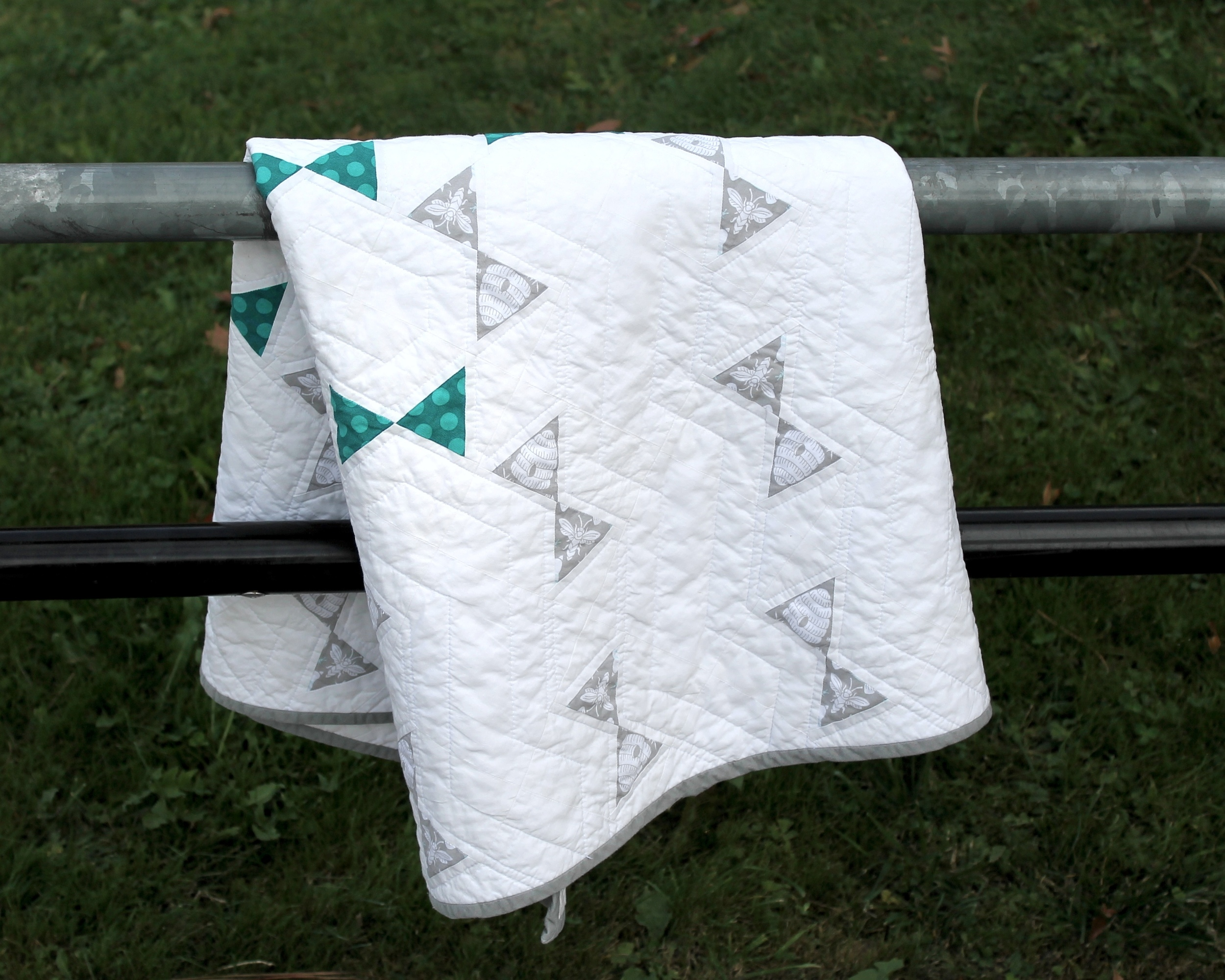 Gray and teal modern baby quilt draped on a fence