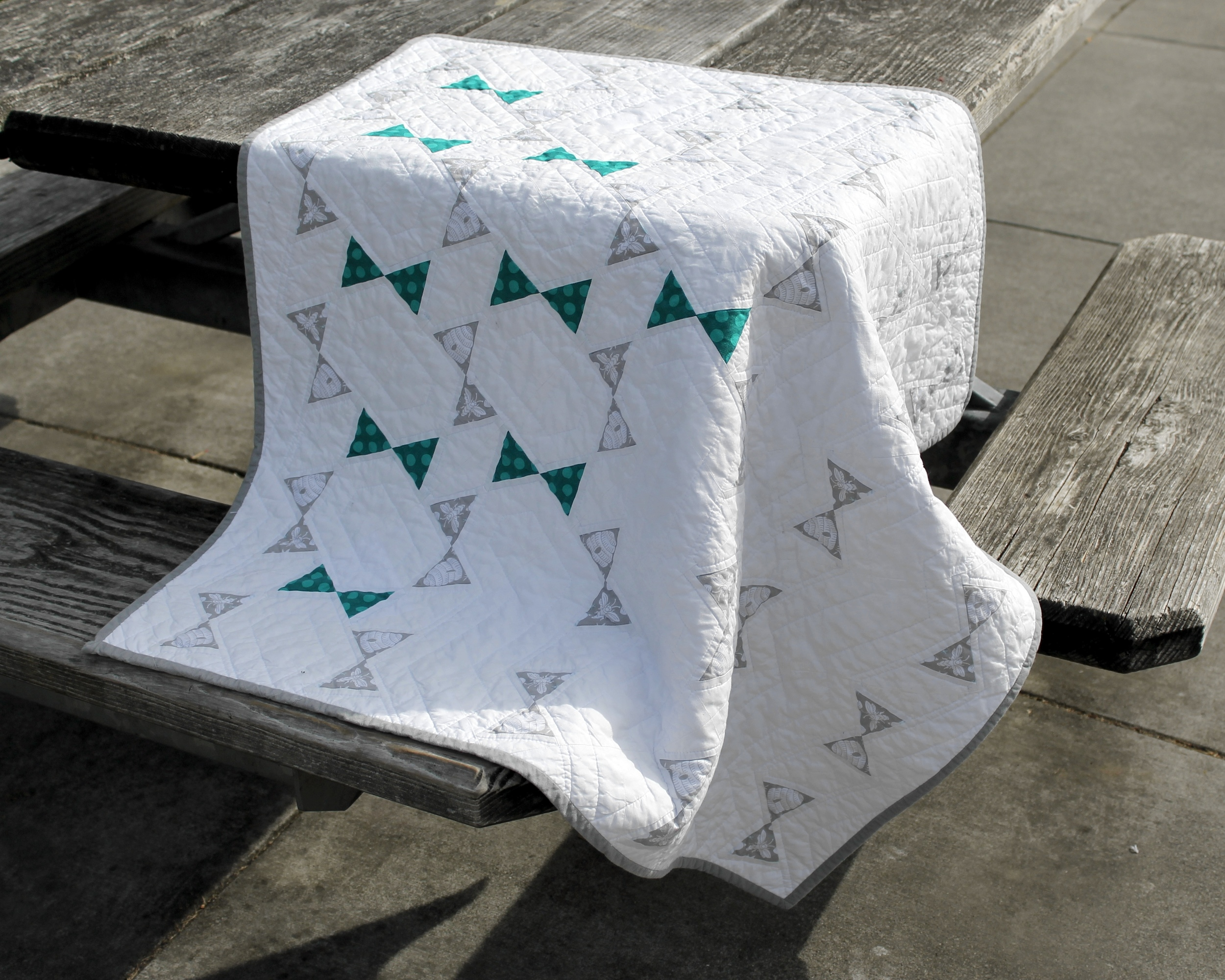 Gray and teal modern quilt draped on a table