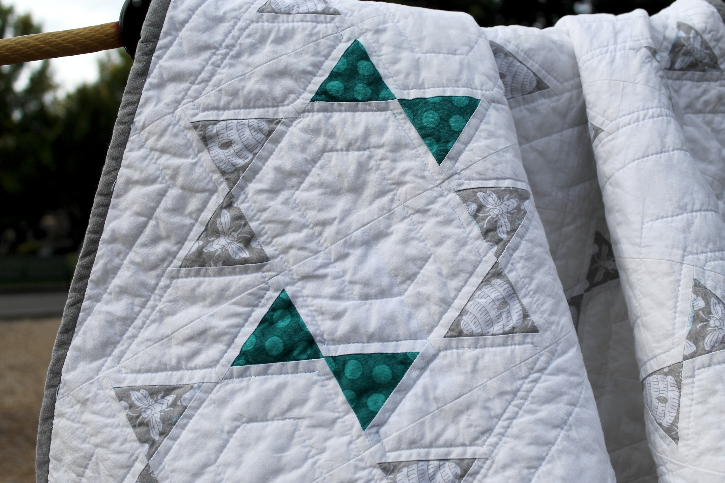 Close up of gray and teal blocks on modern baby quilt