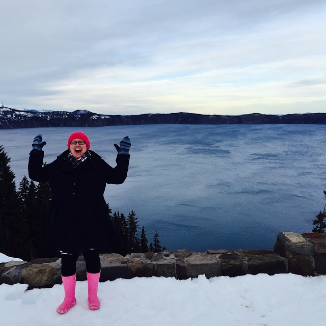 Girl standing in front of Crater Lake in hand knit pink hat and pink boots