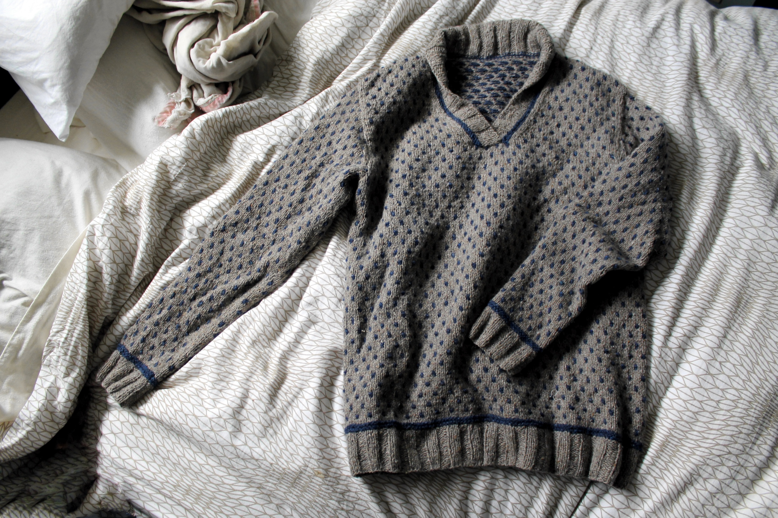 Warwick sweater made with light brown and navy tweed yarn, laying on a bed