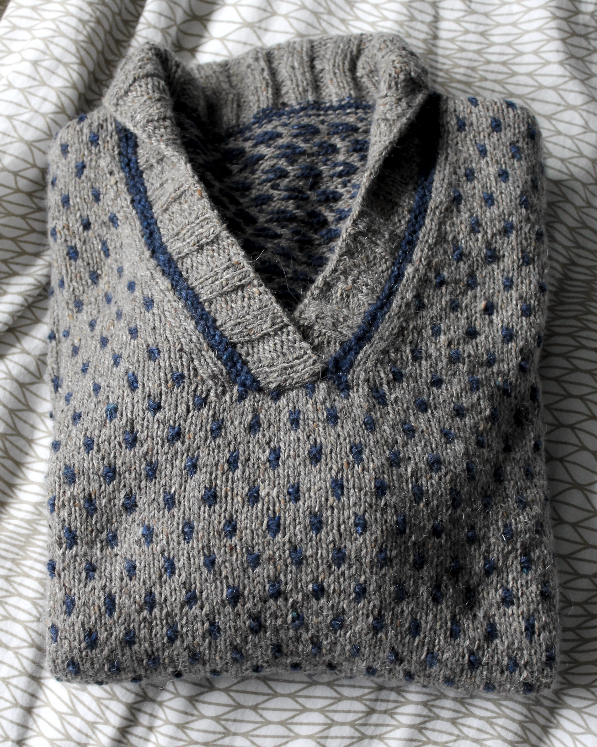 Close up of folded Warwick Sweater in light brown and navy tweed yarn from Berroco