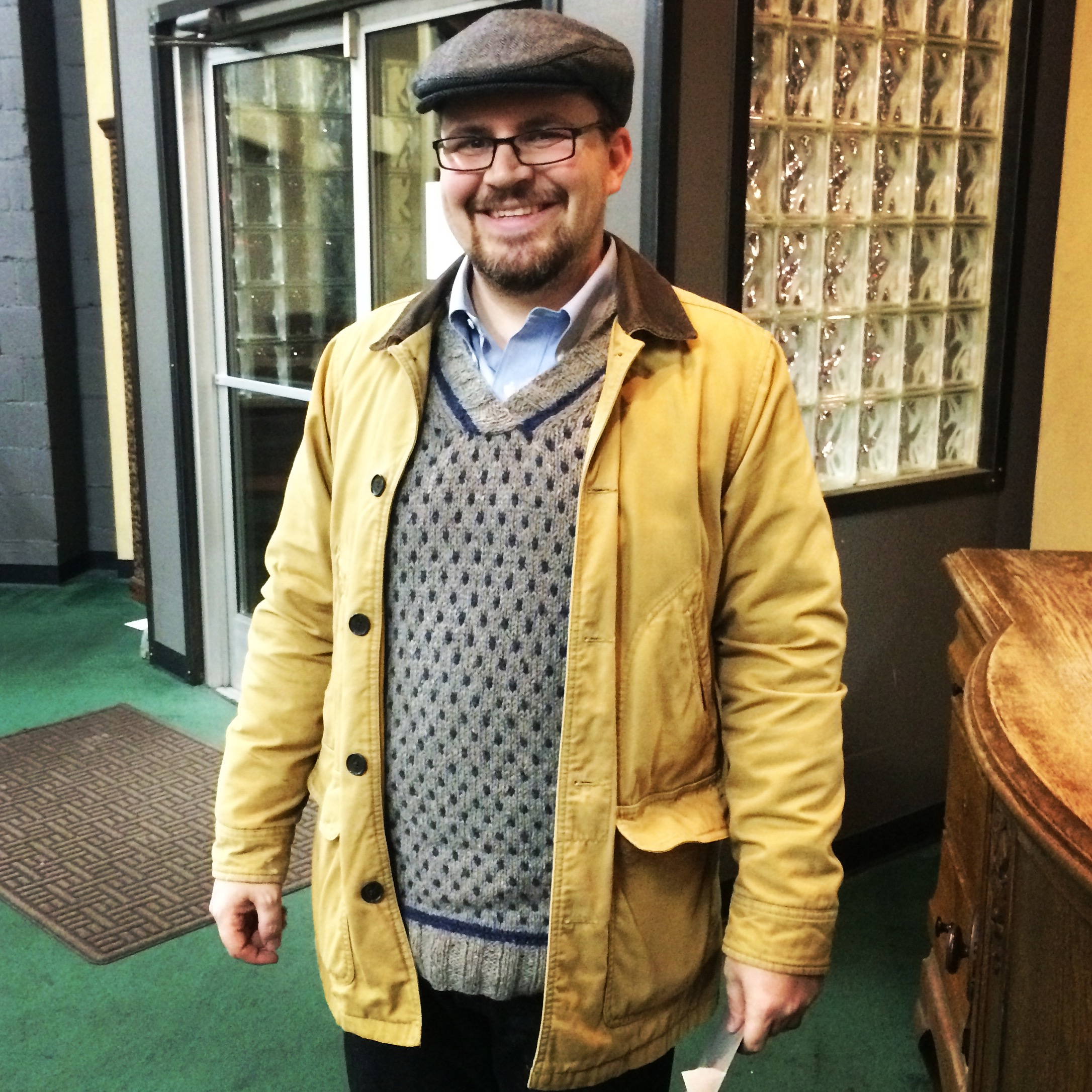 Man wearing Warwick sweater in light brown and navy tweed yarn from Berroco