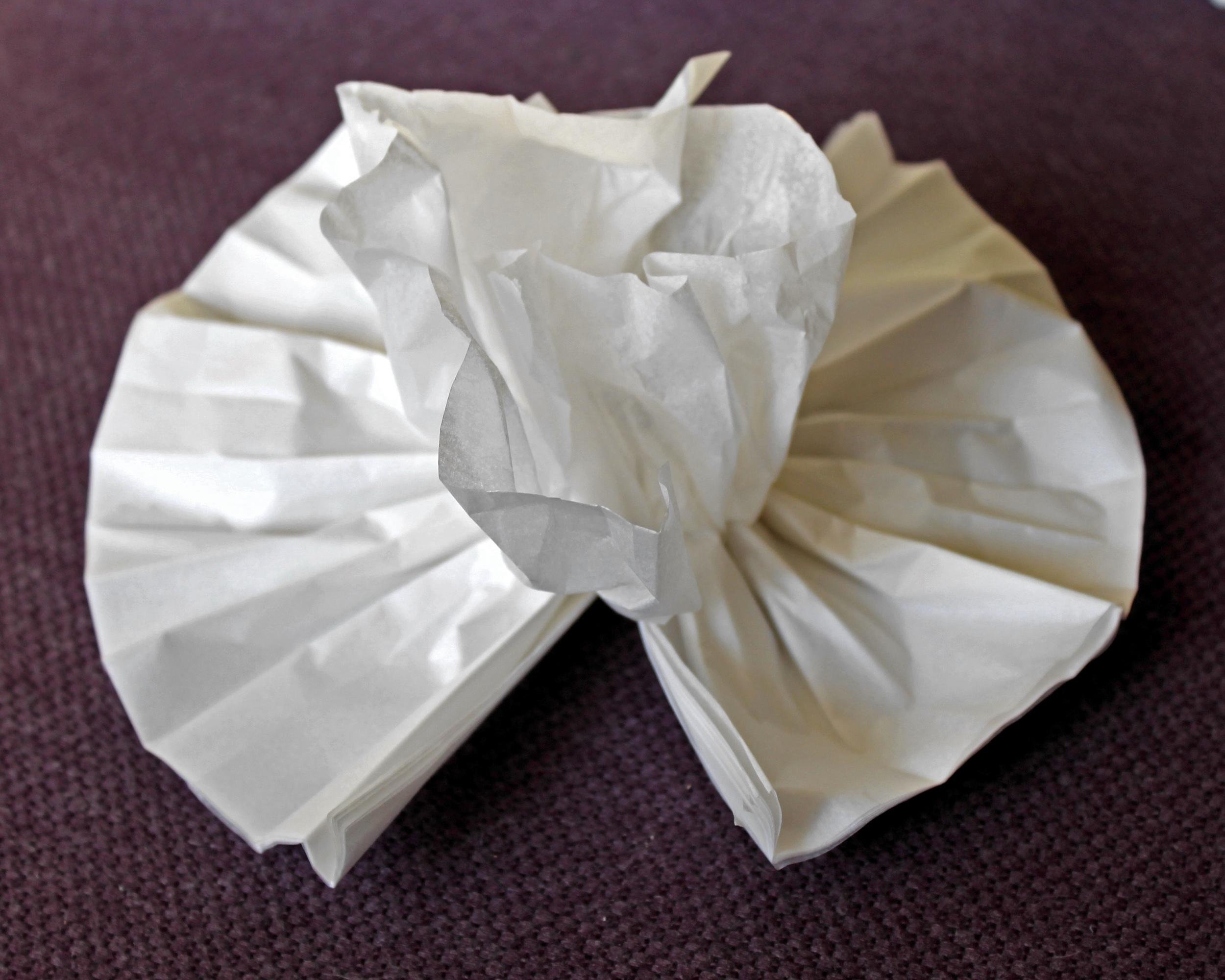 Half finished white tissue paper flower