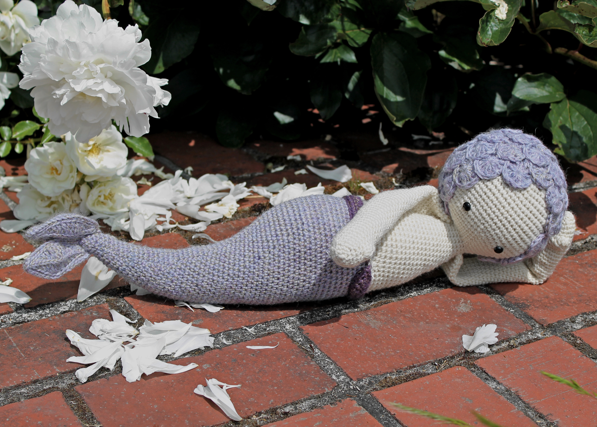 Purple Lalylala Mici the Mermaid laying on bricks