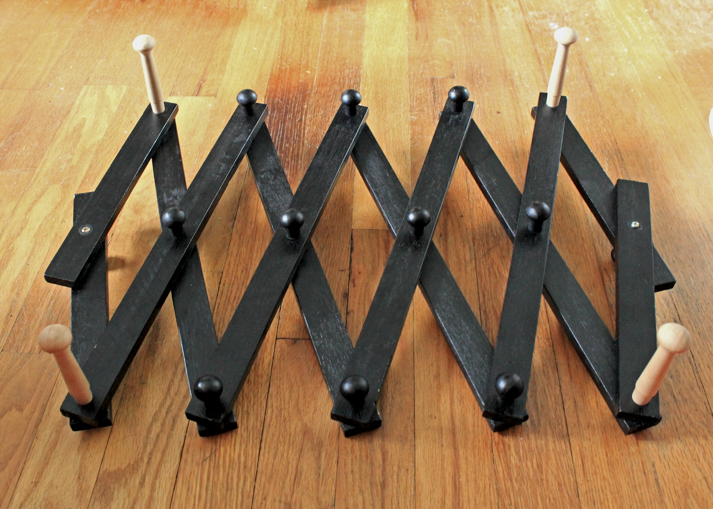 Shoe rack with 4 long wooden pegs (part of a DIY yarn swift)
