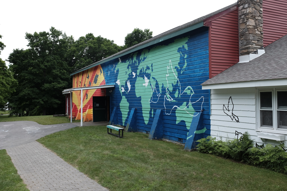 The campus covers about 100 acres in historic Rhinebeck, NY. Pictured here is Main Building, which houses an indoor gym, the dining hall, bathrooms, and a campers' lounge. The mural on the side was painted by campers.