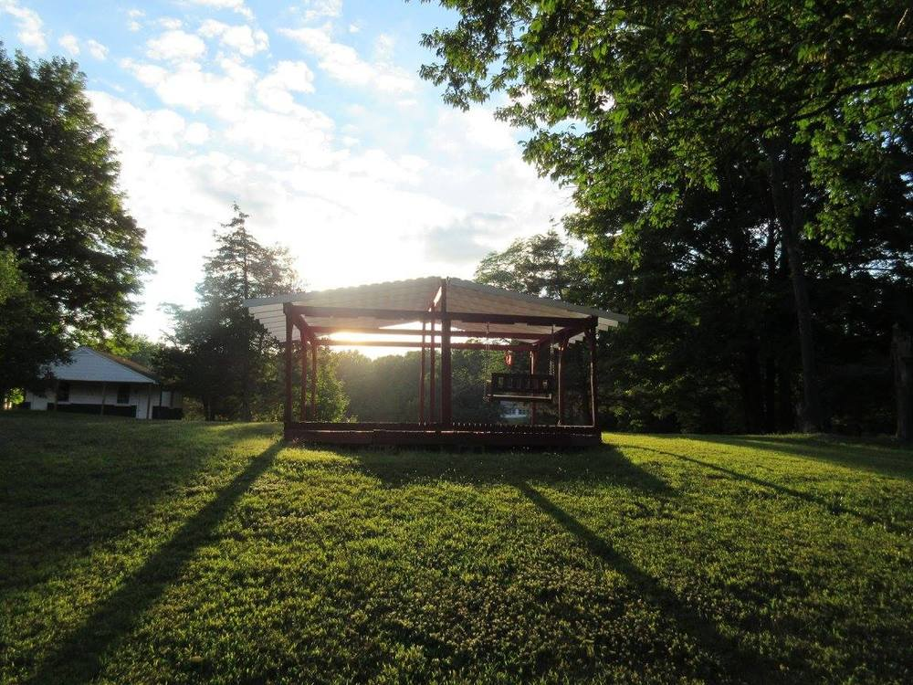 A camper built gazebo sits atop Cabin Hill, surrounded by Art, Drama, Hiking, and Projects Cabins,