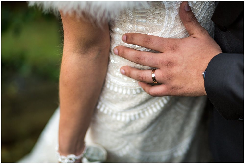 close up of grooms hand on brides waist