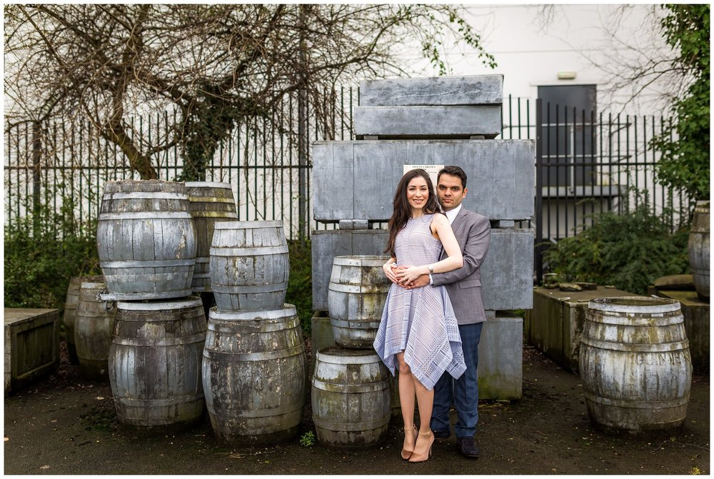 couple cuddling in front of barrels