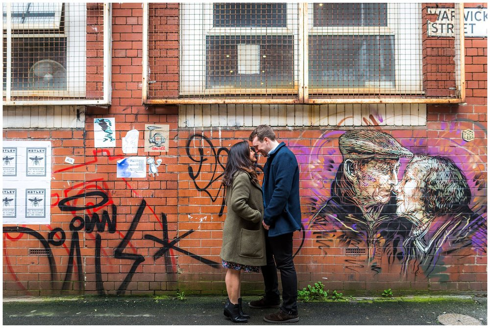 wide shot of couple with graffiti background