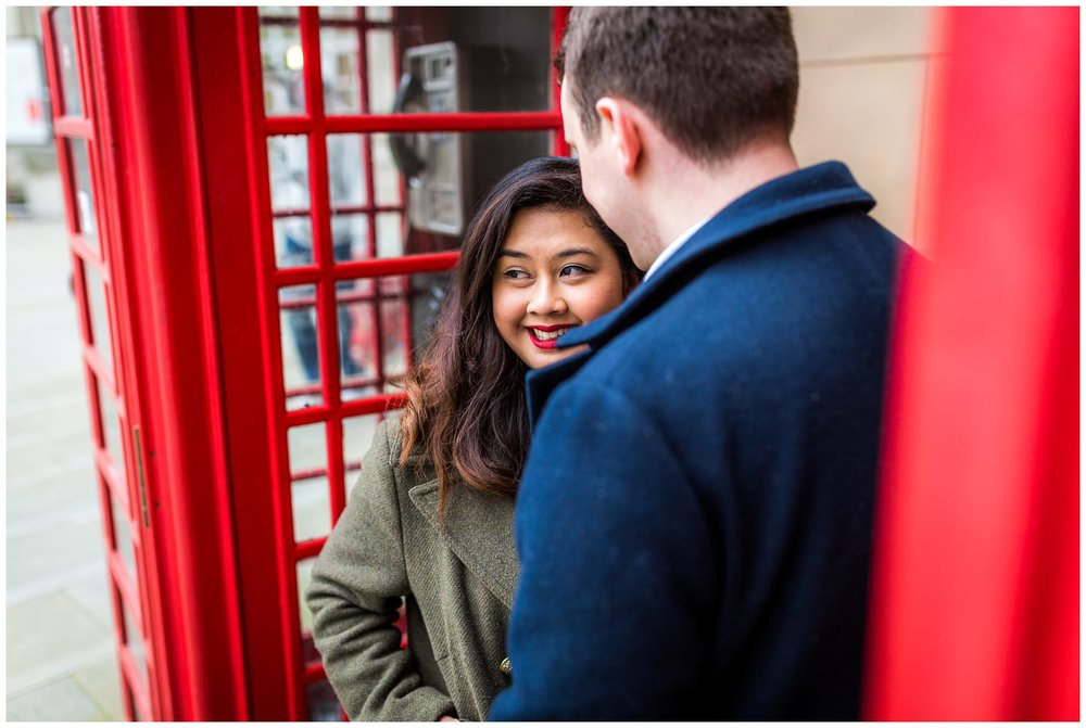 couple between old red phone boxes