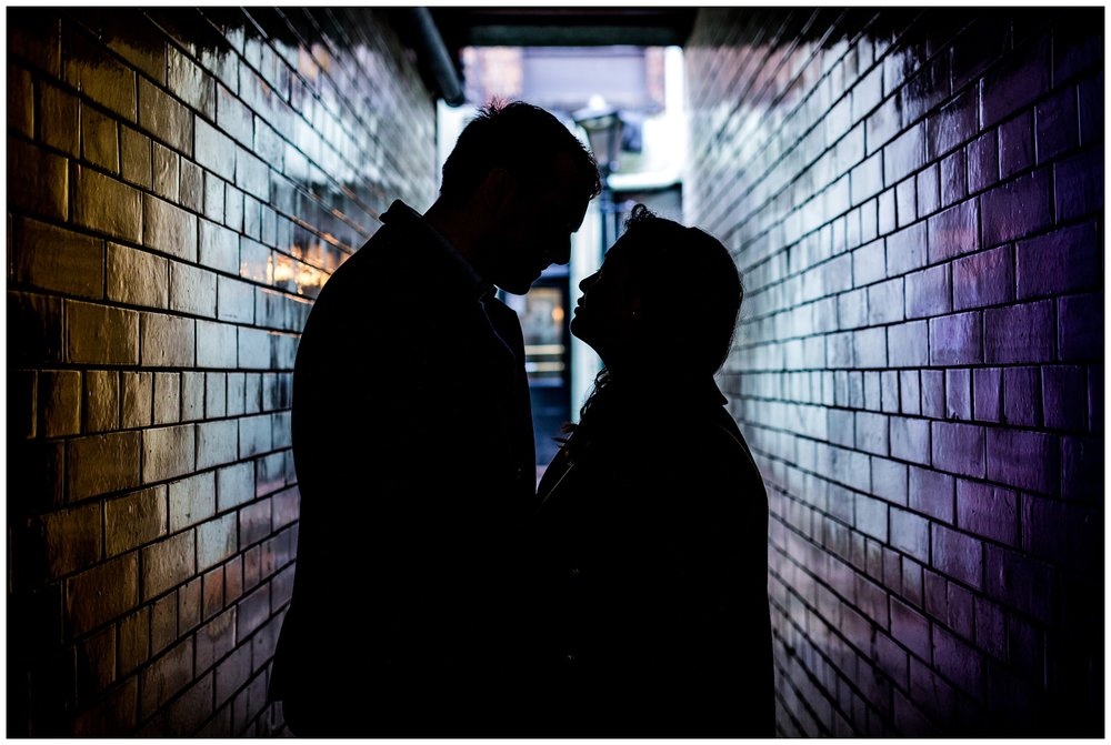 silhouette of couple down alley