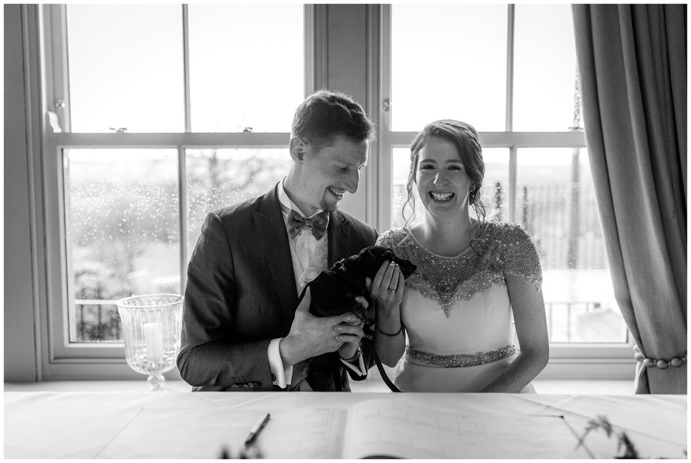 bride and groom signing the register with their dog