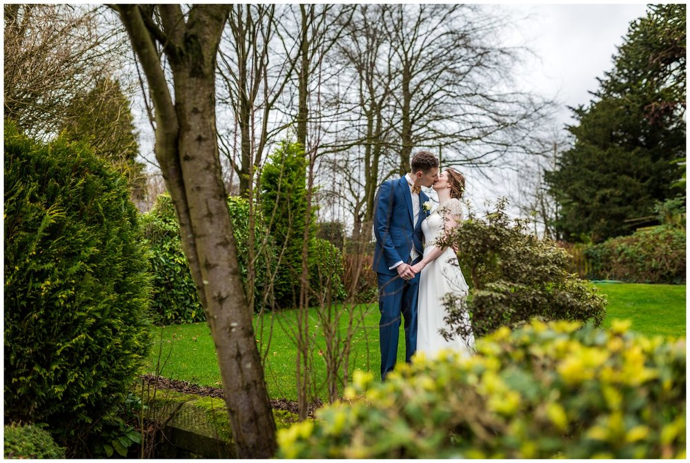 bride and groom kissing in gardens