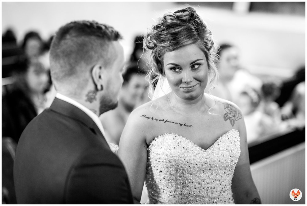 bride looking at groom during service
