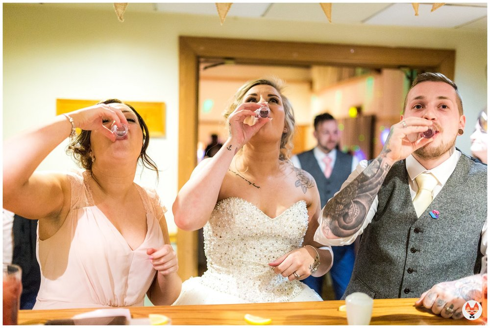 bride and groom doing shots at the bar