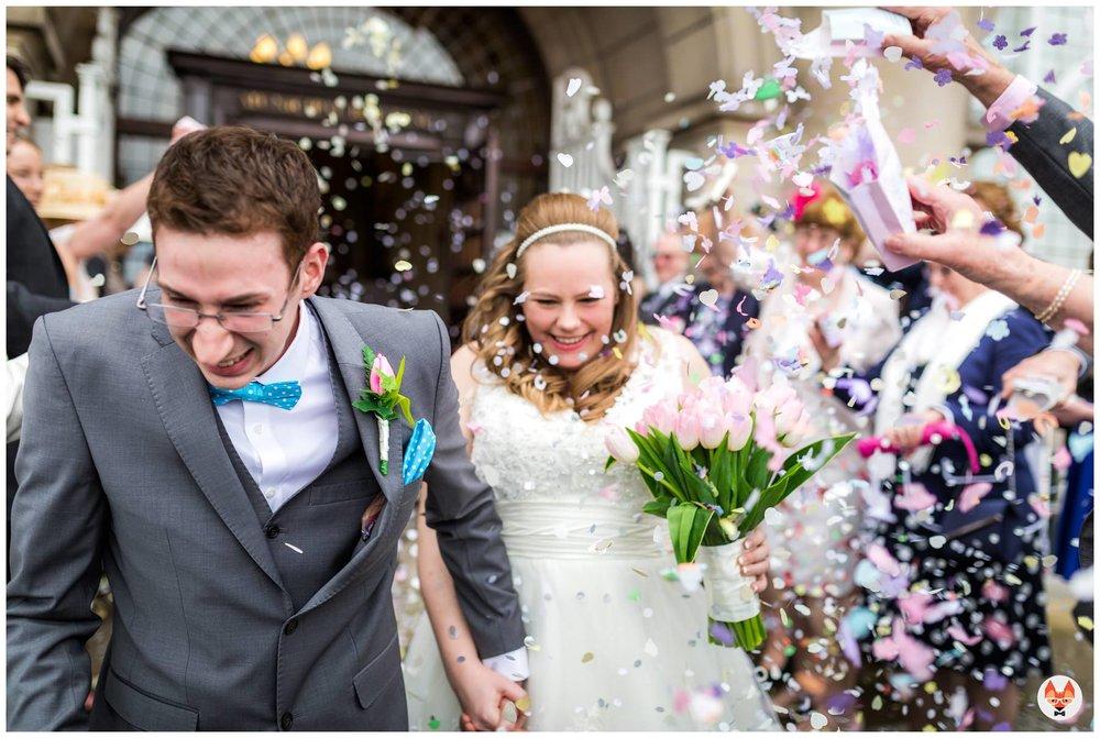 bride and groom run through confetti