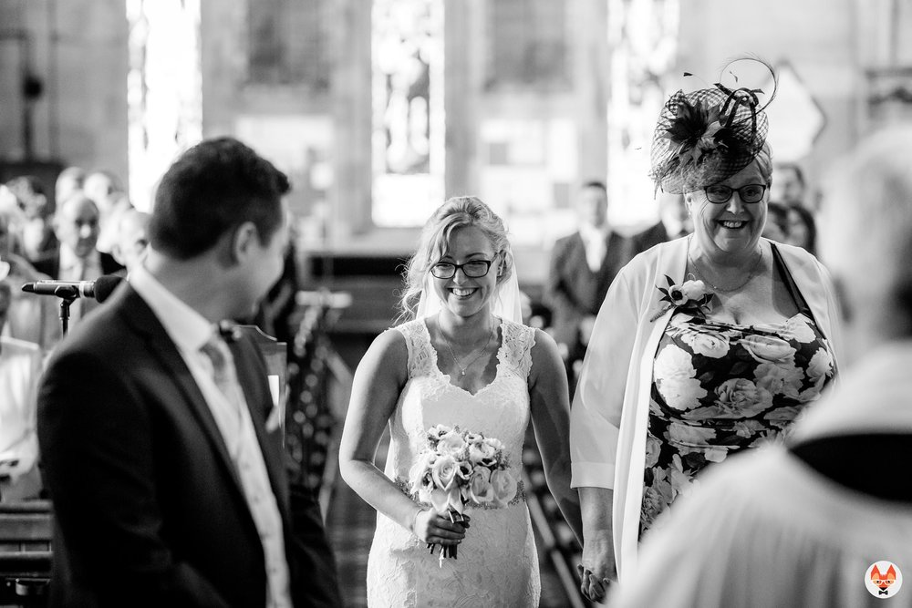 bride smiling as she walks up the aisle