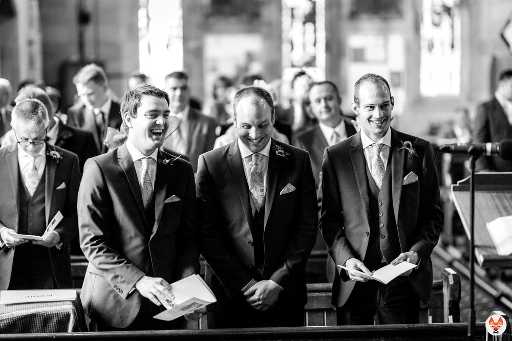 groomsmen laughing during the service