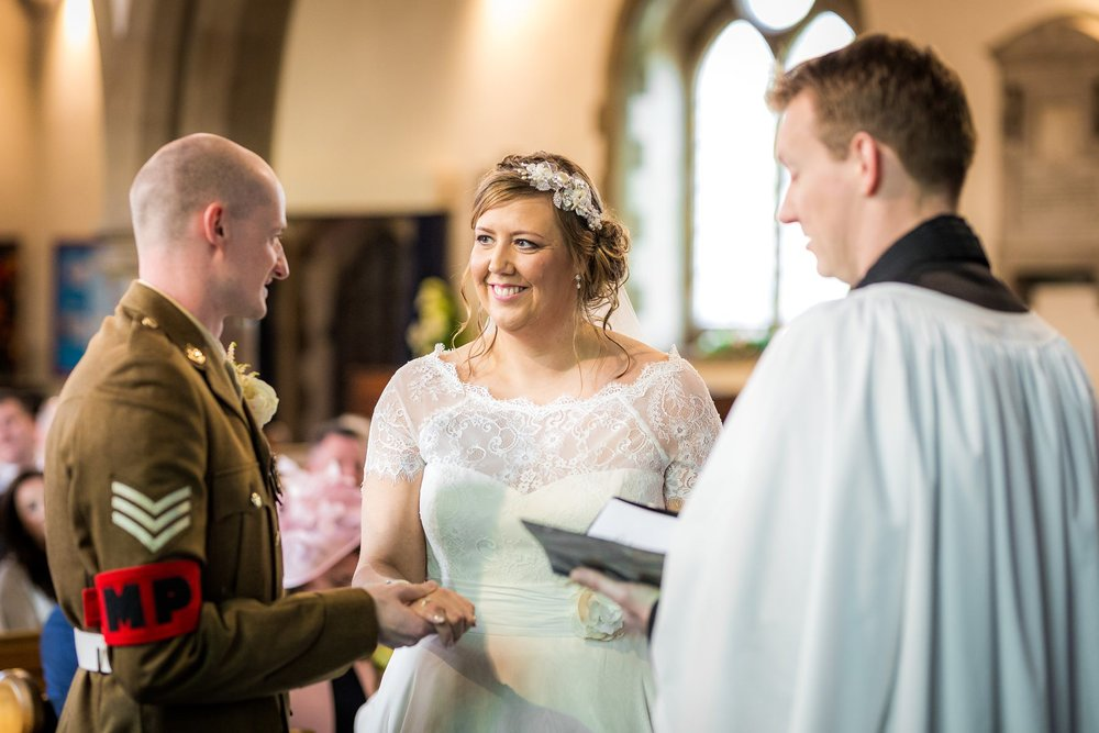 bride and groom smiling during wedding service