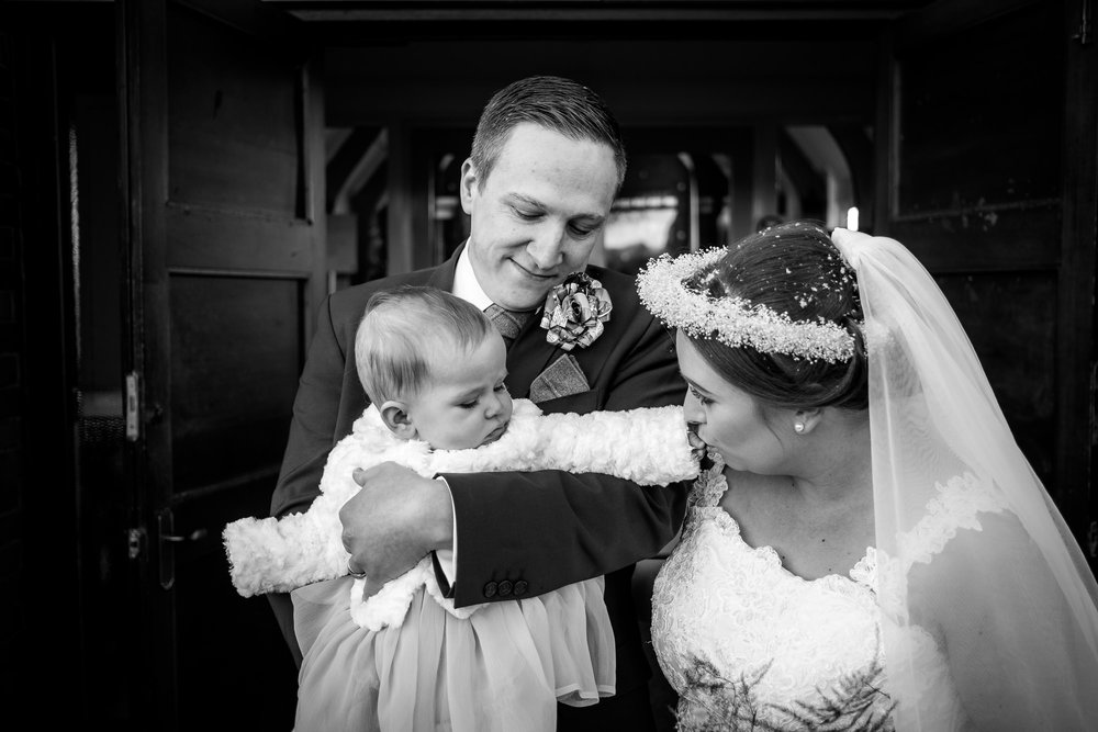 bride and groom with their daughter