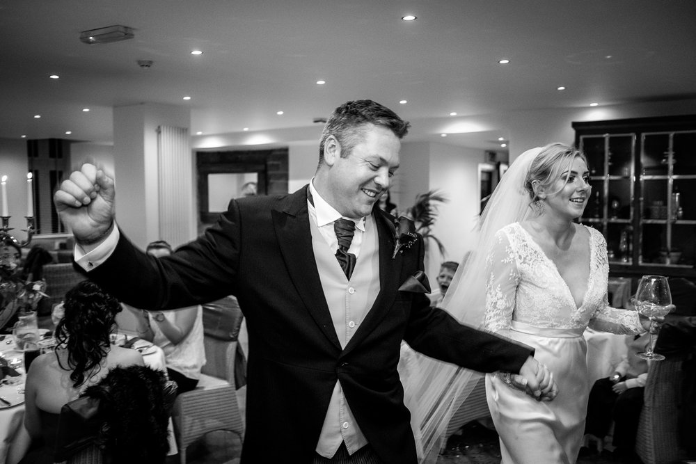 bride and groom dancing on their way into the wedding breakfast