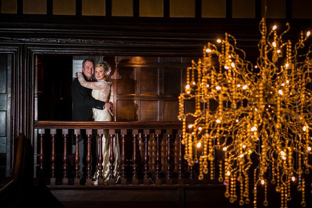 bride and groom in front of chandelier