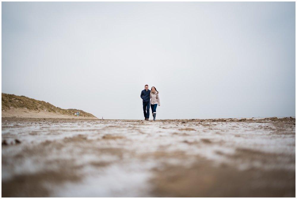 low shot of couple walking on beach