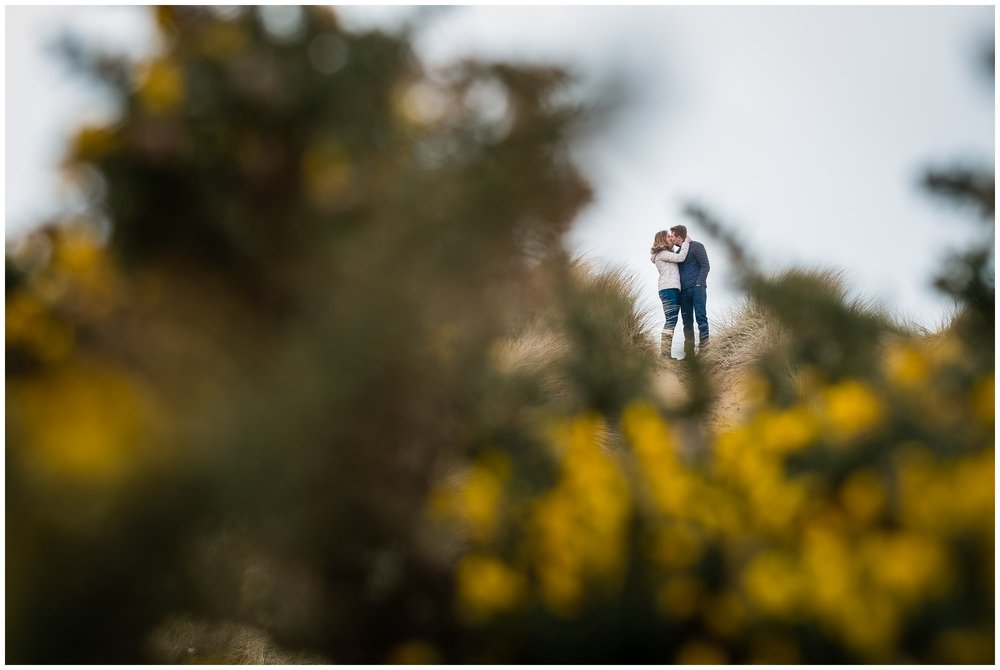 couple kissing between bushes