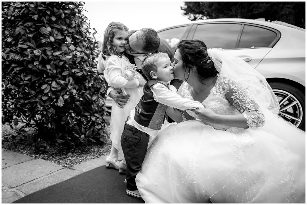 bride and groom kissing their children